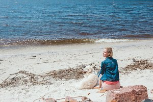 back view of woman sitting on shore