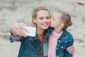 adorable daughter kissing mother whi