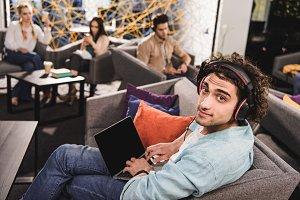 young businessman in headphones sitt