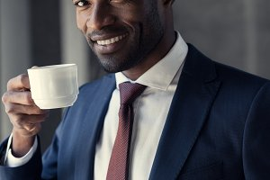 happy young businessman with cup of