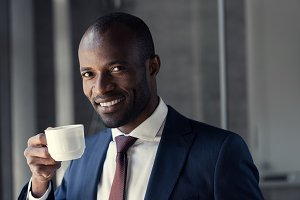 smiling young businessman with cup o