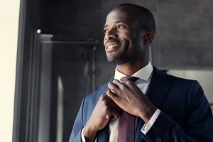 smiling young businessman putting on
