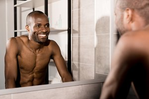 happy young man looking at mirror in