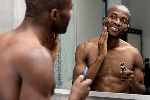 smiling african american man shaving