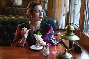 Woman in a cafe eats ice cream.
