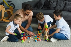 father and kids playing with wooden