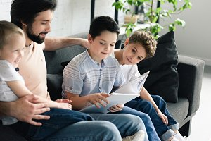 side view of father and sons reading