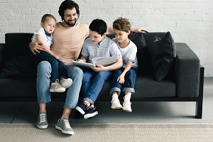 smiling father and sons reading book