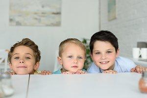 little boys hiding behind table and