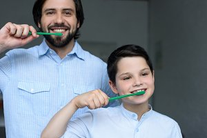 portrait of father and son brushing
