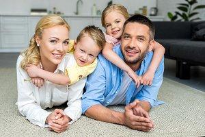 happy family lying on carpet and smi