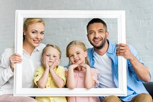 happy family holding frame and smili