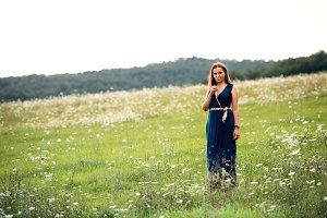 A young woman standing in nature on