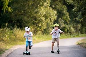 Two small boys with a helmet riding