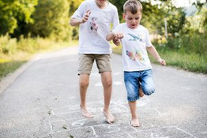 Two small boys hopscotching on a