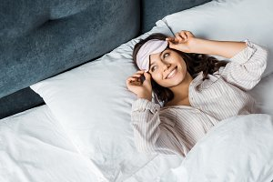 smiling girl in sleeping mask waking