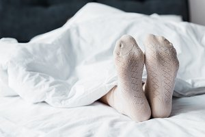 cropped view of girl in socks lying