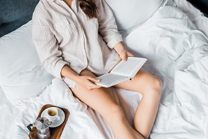beautiful girl reading book in bed w
