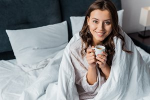 smiling girl with cup of coffee sitt