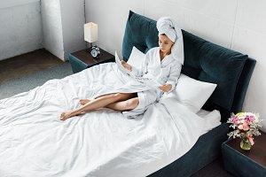 attractive girl in bathrobe reading
