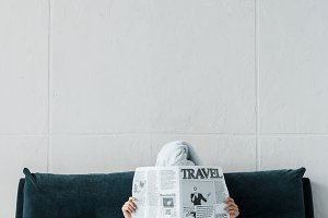 woman reading travel newspaper on be