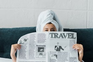 young woman hiding behind travel new