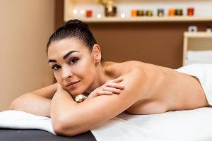 beautiful young woman lying on massa