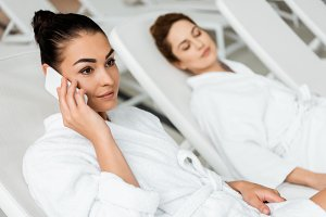 smiling young woman in bathrobe talk