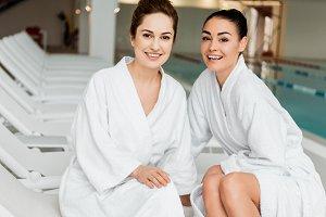 happy young women in bathrobes smili