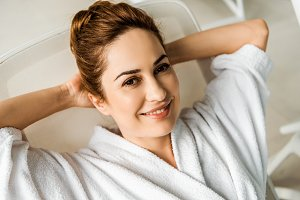 happy young woman in bathrobe lying