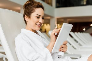 smiling young woman in bathrobe usin