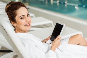 young woman in bathrobe using digita