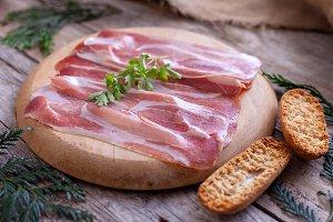Sliced Serrano ham on wooden board a