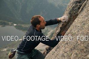 A brave young man climbs a high rock