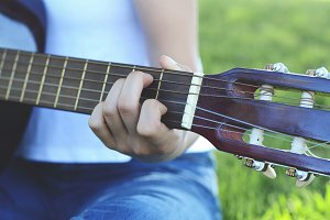 Woman playing guitar at the park.