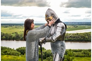 The lady puts on her knight a helmet