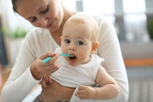 Mom feeds baby with spoon, cozy real