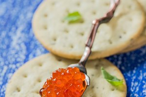 Red caviar in spoon on crackers