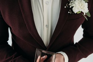 partial view of groom in suit with b