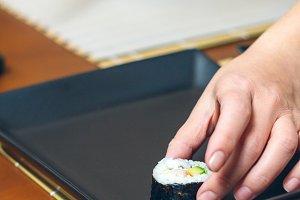 Woman chef placing japanese sushi ro