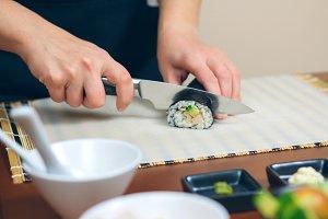 Closeup of woman chef cutting japane