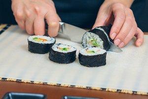 Female chef cutting japanese sushi r