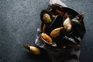 Fresh mussels in black ceramic bowl