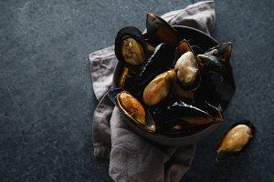 Fresh mussels in black ceramic bowl