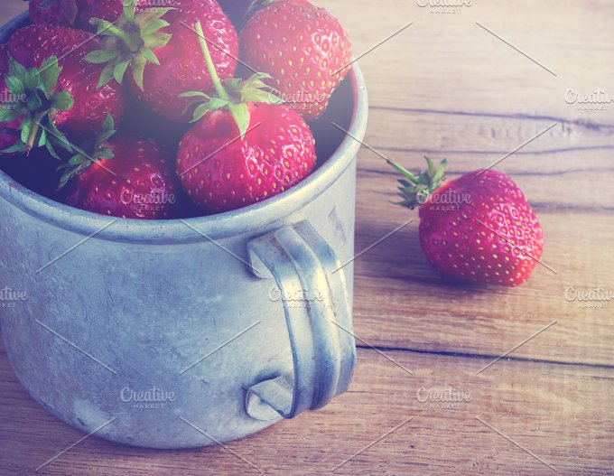Ripe strawberries in a metal mug. Old wooden table. - Food & Drink