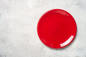 Red plate on light stone table.