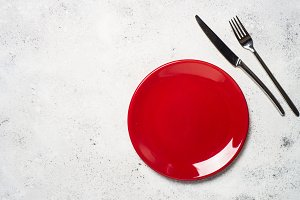 Red plate and cutlery  on light ston