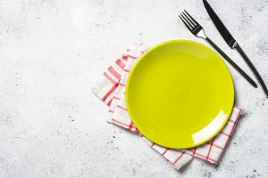 Green plate, cutlery and tablecloth