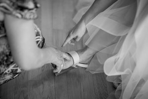 Bride puts on wedding shoes on feet