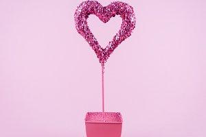 Glitter heart in flower pot on pink